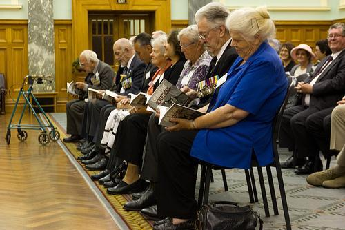 """Guest veterans and family representatives viewing the book<p class=""""detail-small"""">Ministry for Culture and Heritage</p>"""